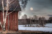 stock photo of shacks  - Old red barn in a countryside landscape with full moon - JPG