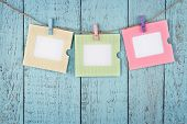 stock photo of clotheslines  - Three empty colorful photo frames or notes paper hanging with clothespins on wooden blue vintage shabby chic background - JPG