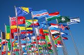 stock photo of placard  - Flags of all nations of the world are flying in blue sunny sky - JPG