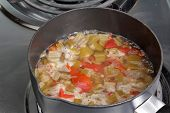 picture of okras  - Okra and tomato mix stewing in sauce pan on electric stove in preparation for addition to a larger pot of Creole Chicken Gumbo - JPG