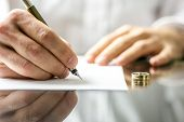 picture of cheating  - Closeup of a man signing divorce papers - JPG