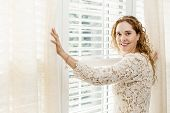 pic of lace-curtain  - Happy woman opening curtains on big sunny window with shutters - JPG