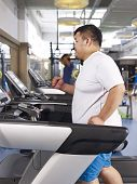 picture of obese man  - an overweight young man running on treadmill in fitness center - JPG