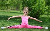 stock photo of legs apart  - Little girl in pink performs exercise splitting legs apart on grass at day outdoors - JPG