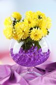 Beautiful flowers in vase with hydrogel on table on bright background poster