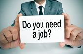image of enterprise  - a man wearing a suit holding a signboard with the question do you need a job written on it - JPG