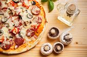stock photo of champignons  - Whole baked pizza on wooden board - JPG