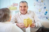 foto of congrats  - Portrait of mature man giving present to his wife - JPG