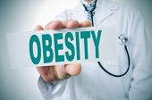 foto of obese  - a doctor showing a signboard with the word obesity written in it - JPG