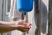 stock photo of lavabo  - Closeup of gardener girl woman with red nails wash hands under rural plastic washer tool water - JPG