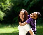 picture of piggyback ride  - Portrait of a single mother with son enjoying piggyback ride outdoors - JPG