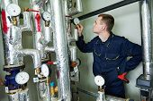 foto of manometer  - repairman engineer or inspector of fire engineering system or heating system with valve equipment in a boiler house - JPG