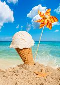 foto of vanilla  - Vanilla flavor icecream with pinwheel on summer beach - JPG