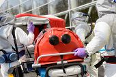 stock photo of decontamination  - Biohazard medical team pushing stretcher towards decontamination chamber - JPG