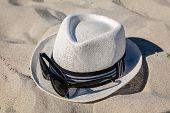 stock photo of fedora  - White straw fedora hat on sandy beach with black rimmed polarized sunglasses - JPG