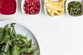 picture of pesto sauce  - Arugula salad with pomegranate seeds and sauce pesto sauce and freshly cut avocado in bowls on white background  - JPG