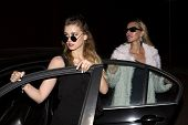 stock photo of starlet  - two women with sunglasses getting out of their car in the night - JPG