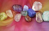 pic of chakra  - A selection of tumbled chakra gemstones laying on rainbow chiffon material - JPG