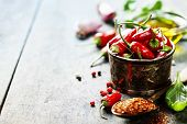 stock photo of chili peppers  - Red Hot Chili Peppers with herbs and spices over wooden background  - JPG