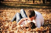 foto of hand kiss  - Kissing young couple in love in the autumn park - JPG