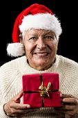 image of coy  - Friendly male pensioner with red Father Christmas hat and white pullover - JPG
