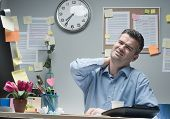 pic of stiff  - Tired businessman sitting at desk touching his painful neck - JPG