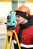 image of geodesic  - One surveyor worker working with theodolite transit equipment at road construction site outdoors - JPG
