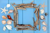 picture of driftwood  - Sea shell collage and driftwood frame over wooden blue background - JPG