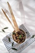 foto of ladle  - Presentation of a small group of black olives on wooden ladle - JPG
