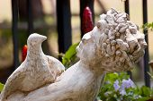 stock photo of garden sculpture  - Sculpture in a garden of a bird and an infant - JPG