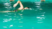 stock photo of crawling  - Swimming. Competition and recreation. Woman swimmer breathing performing crawl style. Poolside.