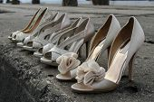 stock photo of pink shoes  - Dressy pink high heel wedding shoes lined up on stone pier during wedding photo shoot - JPG
