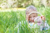 pic of easter eggs bunny  - little smiling boy holding basket with easter eggs and bunny after egg hunt in the park lying in the grass - JPG