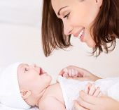 foto of mother-in-love  - Closeup portrait of beautiful cheerful mother playing with cute little baby lying down on the bed - JPG