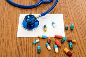 stock photo of prescription  - prescription with colorful pills and stethoscope on wooden ground - JPG