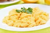 stock photo of egg whites  - Scrambled eggs on white plate close up view - JPG