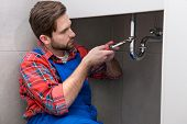 picture of plumber  - Young plumber is repairing a sink at the bathroom - JPG