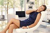 image of  eyes  - Attractive young brunette caucasian woman in blue dress resting in leather chair at trendy home - JPG