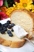 picture of pound cake  - Slice of pound cake with blueberries and spoon topped with whipped cream and flowers in the background - JPG