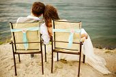 image of married couple  - Romantic young newlyweds couple sitting near water on the beach resting after wedding ceremony - JPG