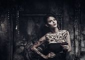foto of old lady  - Tattooed beautiful woman in old spooky interior - JPG