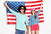 stock photo of funky  - Funky young couple smiling and looking at camera while standing against American flag - JPG