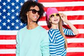 picture of shot glasses  - Funky young couple wearing glasses and smiling while standing against American flag - JPG