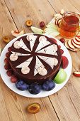 stock photo of hot-chocolate  - big whole frost chocolate cream brownie cake topped with white chocolate and cream flowers with hot tea cup decorated with fruits apple plum and grape on plate on wooden table - JPG