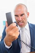 stock photo of yell  - Businessman yelling at his phone in his office - JPG