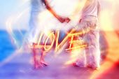 pic of surreal  - Beautiful love couple standing barefoot holding hands on a jetty by the sea in the Maldives with a dreamy surreal effect and word  - JPG