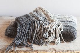 pic of tassels  - wool grey scarf with tassels closeup on wooden background - JPG