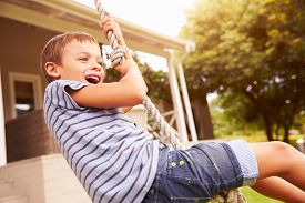 pic of swing  - Smiling boy swinging on a rope at a playground - JPG