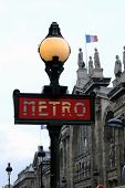 picture of gare  - Sign for the Paris Metro with the Gard du Nord in the background with the french flag - JPG