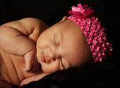 stock photo of newborn baby girl  - Newborn Baby Sleeping on a Soft Black Blanket - JPG